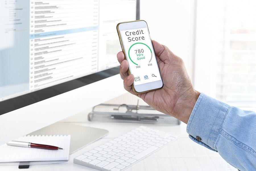 man cin front of laptop while checking his credit score on mobile phone